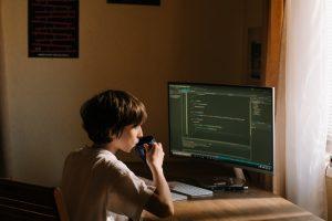 Vrouw kijkend naar codes op computer